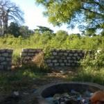 Mauer hinter der Feuerstelle und Dininghall